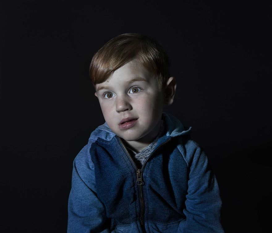 Portrait of a red head boy in blue sweater vacantly staring. He is engrossed in TV.