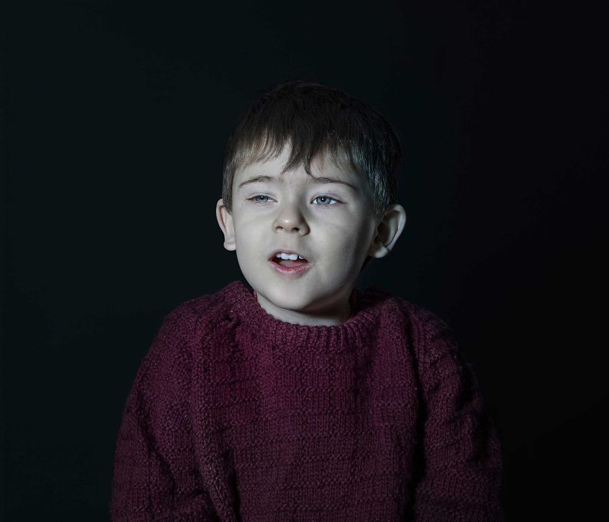 Portrait of a boy in red sweater vacantly staring. He is engrossed in TV.